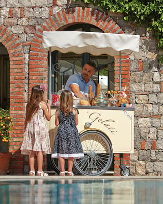 Two little girls ordering ice cream from a poolside gelato stand