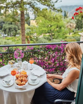 Lady sitting at a balcony breakfast table next to flower-coated railings