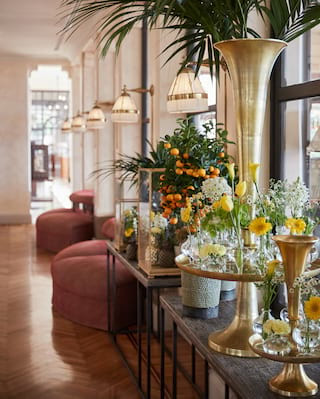 Guest lobby console table covered with white and yellow flowers in gold vases