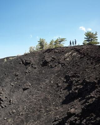 Tourists standing on the dark, rocky slopes of Mount Etna under blue skies