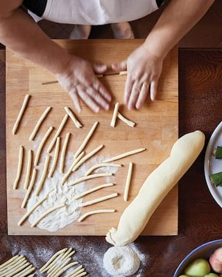 Birds-eye-view of hands rolling bread dough into bread sticks on a wooden counter
