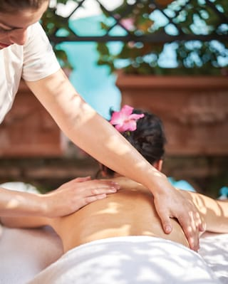 Close-up of hands massaging a lady's back on a massage table