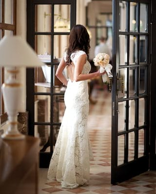 Bride in a fitted wedding dress walking through floor to ceiling glass-panel doors