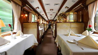 Long view through an elegant train dining car with linen-coated tables