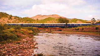 Royal blue train carriages stretching across a bridge over a rocky river