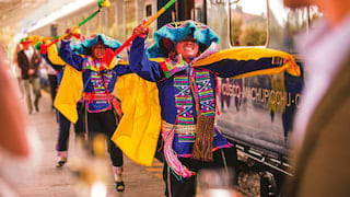 Traditional Peruvian dancers dancing beside royal blue train carriages
