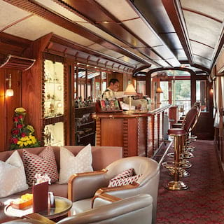 Wood-panelled bar carriage with leather banquette seating and a maroon carpet