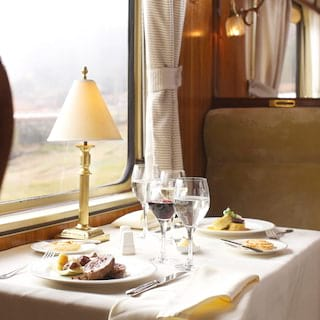 Restaurant car table for two on a train with a lamplit linen-coated table