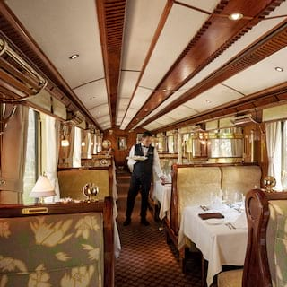 View of a luxurious train dining car with tables lining the sides