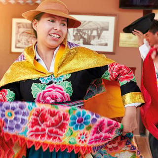 Traditional Peruvian dancer in a floral dress smiling and whirling