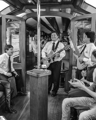 Guitar musicians playing to guests on a luxury train carriage