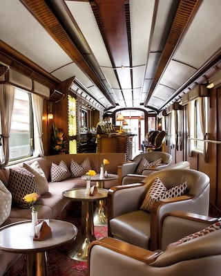 Long view of a train bar carriage with green leather armchairs