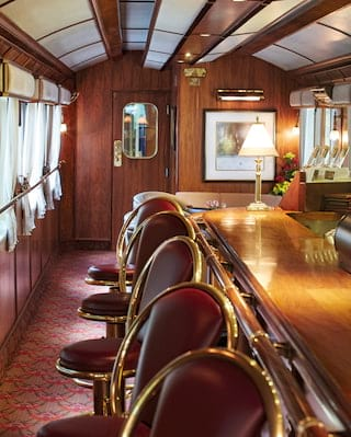 Lamplit train bar car with gleaming polished-wood bar and brass details
