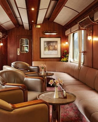 Train bar carriage with dusky pink banquette seating and green leather armchairs