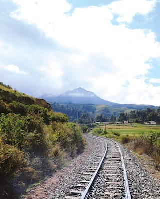 Train tracks winding along a valley towards a Peruvian mountain top