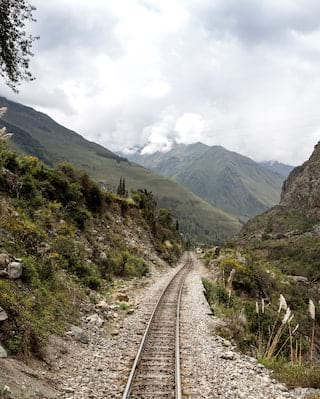 Train tracks stretching into the distance of a valley surrounded by mountains