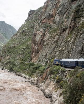 Royal blue train carriages snaking alongside a mountain and rushing river