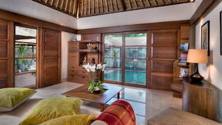 Lounge of a double-height Balinese villa with marble floors and teakwood details