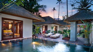 Balinese villas around a freshwater infinity pool surrounded by candles at sunset