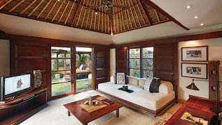 Lounge area in a double-height Balinese villa with a plush daybed