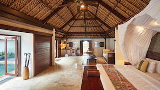 Vast bedroom with a pillowy king-bed under a linen canopy in a double-height villa