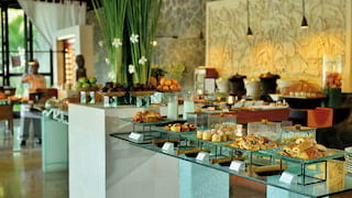 Luxurious breakfast buffet displayed on glass banquet tables in an elegant restaurant