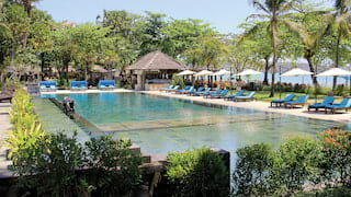 Clear, mirror-still outdoor pool surrounded by sunbeds, parasols and lush palms