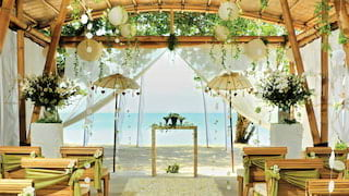 Bamboo pergola over a beach set with rows of chairs and an aisle for a wedding