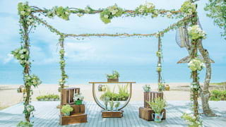 White roses wrapped around a wedding gazebo on a deck overlooking the ocean