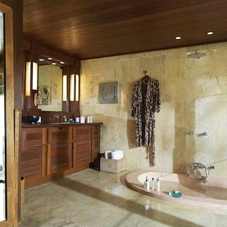 Spacious bathroom with green marble tiles, huge sunken bath and rain shower