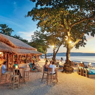 Open-air thatched beach hut bar on a white sandy Balinese beach at sunset