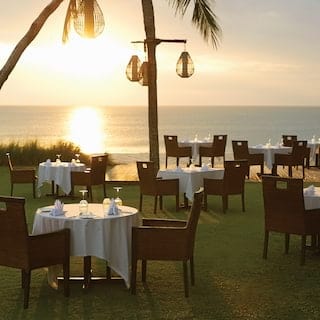View of formal dining tables on a restaurant lawn terrace at sunset over the beach