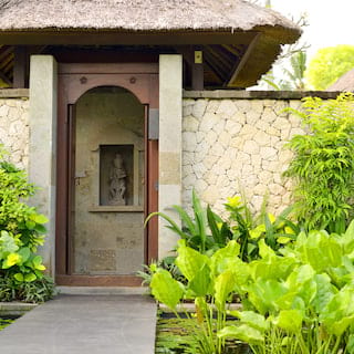 Teakwood gate set into an immaculate stone built wall, edged with lush palm plants
