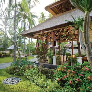 Open-air thatched Balinese villa among lush Asian gardens dotted with palm trees