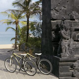 Two bicycles parked next to a traditional Balinese stone statue overlooking a beach