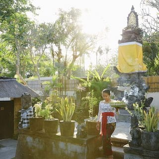 Lady stepping down stone steps from a Balinese statue surrounded by potted palms