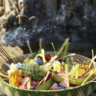Close-up of fried flowers and burning incense in a reed basket next to a statue