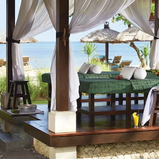 Two massage tables in an open-air pergola with silk drapes and views of the beach