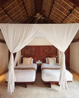 Two single beds under a linen canopy in front of an ornate teakwood headboard