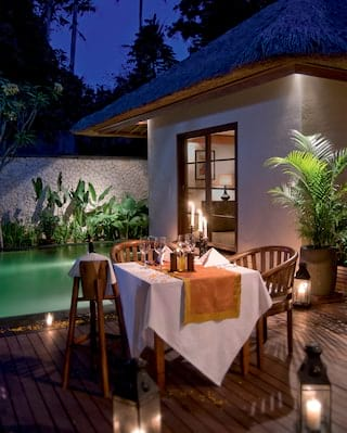Candlelit table for two on a wooden veranda next to a freshwater pool