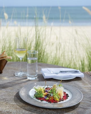Close-up of a salad dish on a table beside a sandy beach