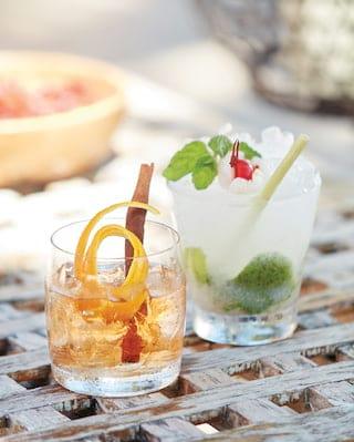 Close-up of one mojito cocktail and one whisky cocktail on a palm weave table