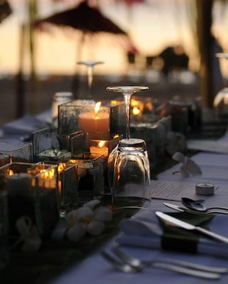 Close-up of glasses and silverware on a table with a candle centerpiece
