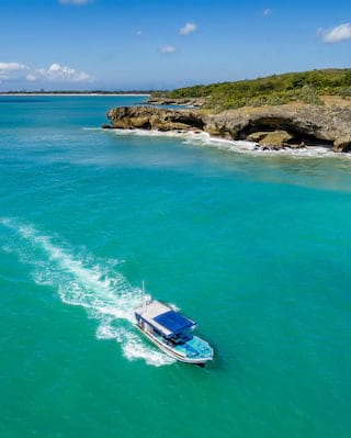 Aerial view of a blue motorboat sailing across turquoise blue waters