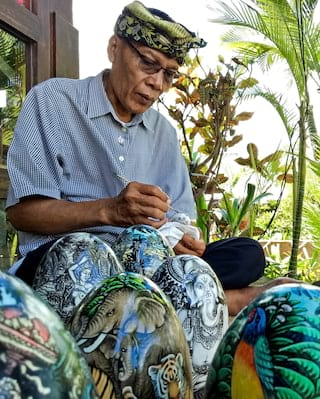 Elderly Balinese man sitting on a veranda painting detailed artwork on stone eggs
