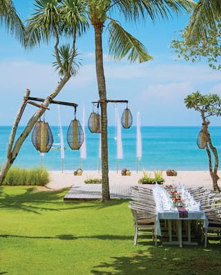 Wedding banquet table on a lawn overlooking the beach surrounded by tall palms