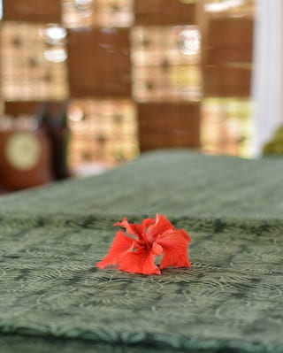 Close-up of a burnt orange coloured hibiscus flower on a green patterned throw
