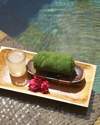 Close-up of a green folded facecloth and a glass of water on a tray beside a pool