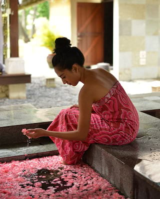 Lady in a pink-patterned bath towel lifting petals from a sunken bath