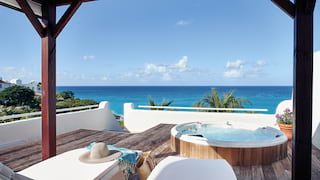 Two sun beds and hot tub under blue skies, with Caribbean sea views